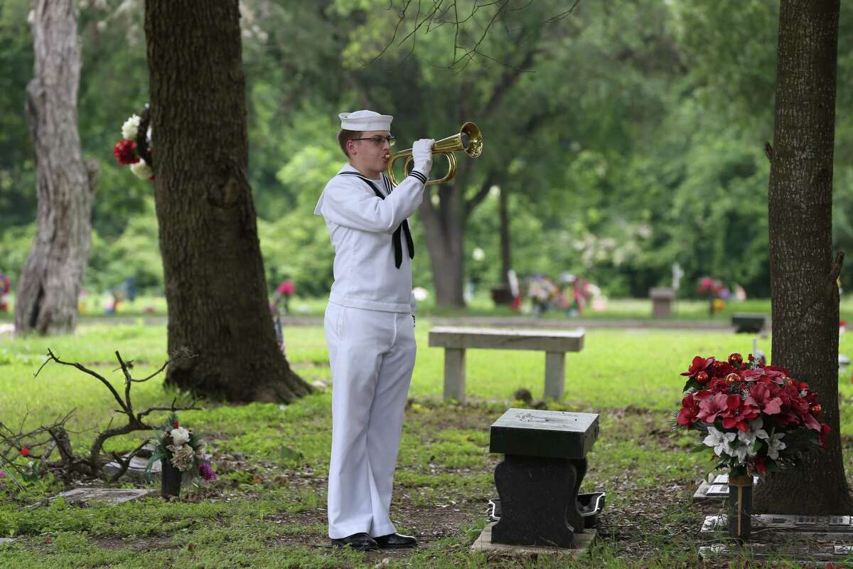 """""""Taps"""" is played at the funeral of William St. John, one of San Antonio's last Pearl Harbor veterans, at Mission Park South Cemetery on Tuesday. St. John, 99, was a Navy radioman 1st class who survived a strafing during the battle."""