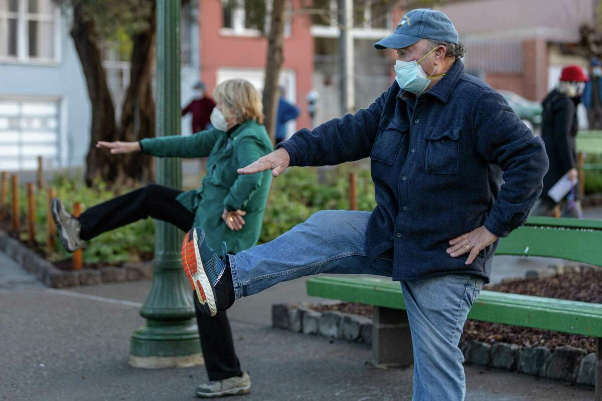 Wes and Doris Watkins wear masks as they practice Tai Chi at a San Francisco park on Friday, January 29, 2021.