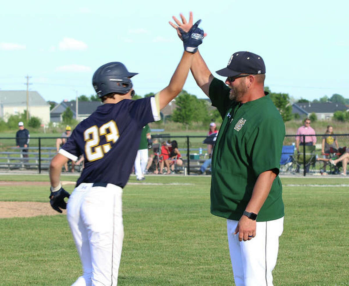 McGivney coach Chris Erwin (right) greets Jacob McKee after McKee's three-run homer in the sixth inning in a Class 1A regional title game Monday in Glen Carbon.