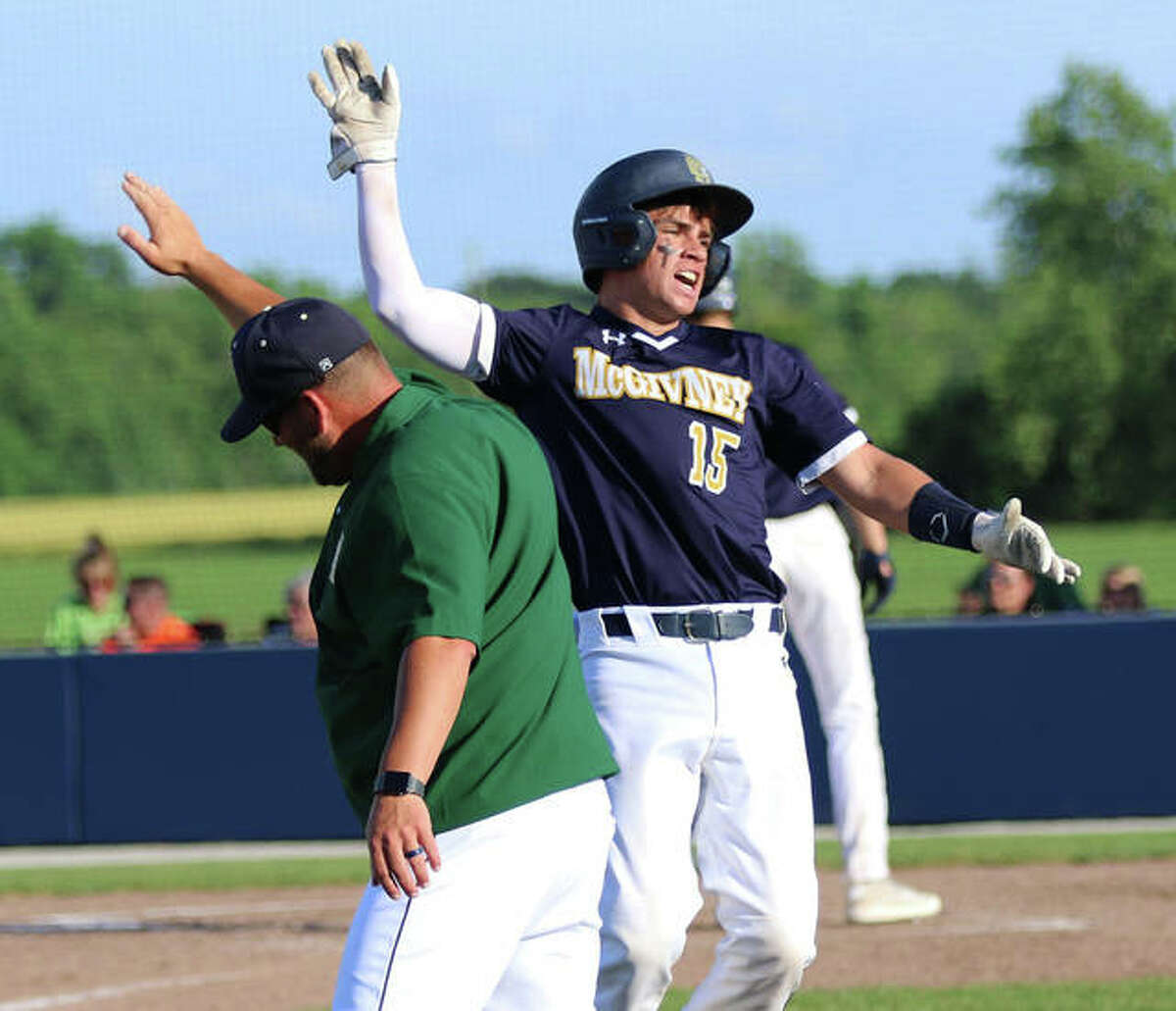 Father McGivney catcher Luke Deakos goes airborne to give coach Chris Erwin a high-five heading back to the dugout in favor of a courtesy runner after his attempt to sacrifice turned into a bunt single in a Class 1A regional title game Monday in Glen Carbon.