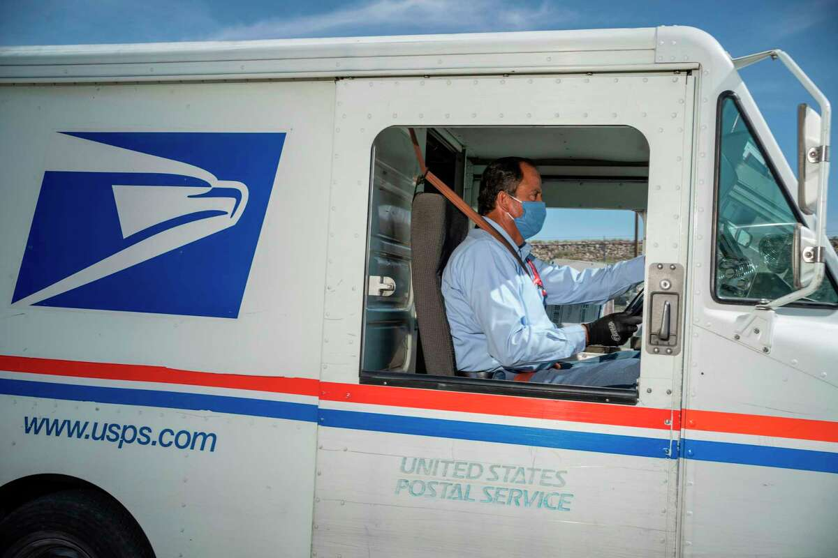 (FILES) In this file photo taken on April 30, 2020 United States Postal Service mail carrier Frank Colon, 59, departs on his delivery route from the Remcon Circle Post Office in El Paso, Texas. (Photo by Paul Ratje / AFP) (Photo by PAUL RATJE/AFP via Getty Images)