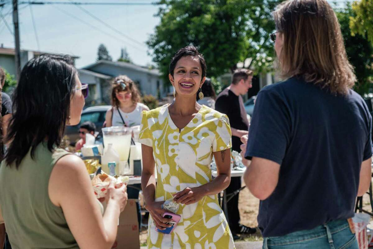 Janani Ramachandran, a social justice attorney, speaks with people at a meet-and-greet in Oakland.