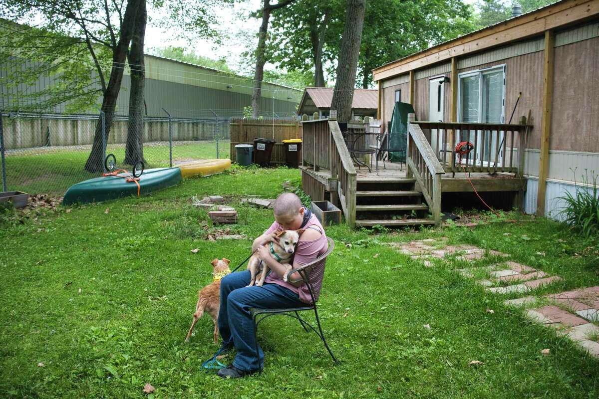 Angela Kaufman and her two rescue dogs, Mugzy, and Spango, outside their mobile home at Saratoga Lakeview Mobile Home Park on Tuesday, June 8, 2021, in Saratoga Springs, N.Y. The mobile home park is being sold to the owner of Boat N RV Condo, whose property is seen on the left in the photo. Kaufman who purchased her home in July of 2020 says that because of the age of her mobile home she fears that it can not be safely moved and if she is forced to leave the park she will have to leave the home behind and will loose everything she has put into her house. (Paul Buckowski/Times Union)