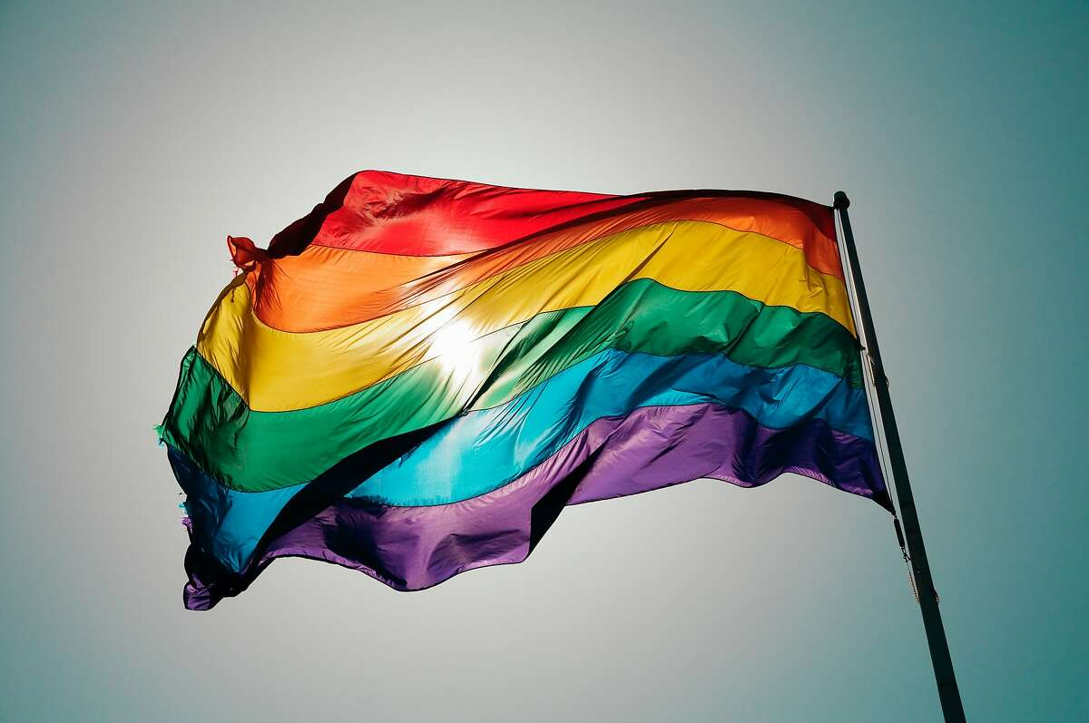 Rainbow Pride flag flies against blue sky in the Castro.