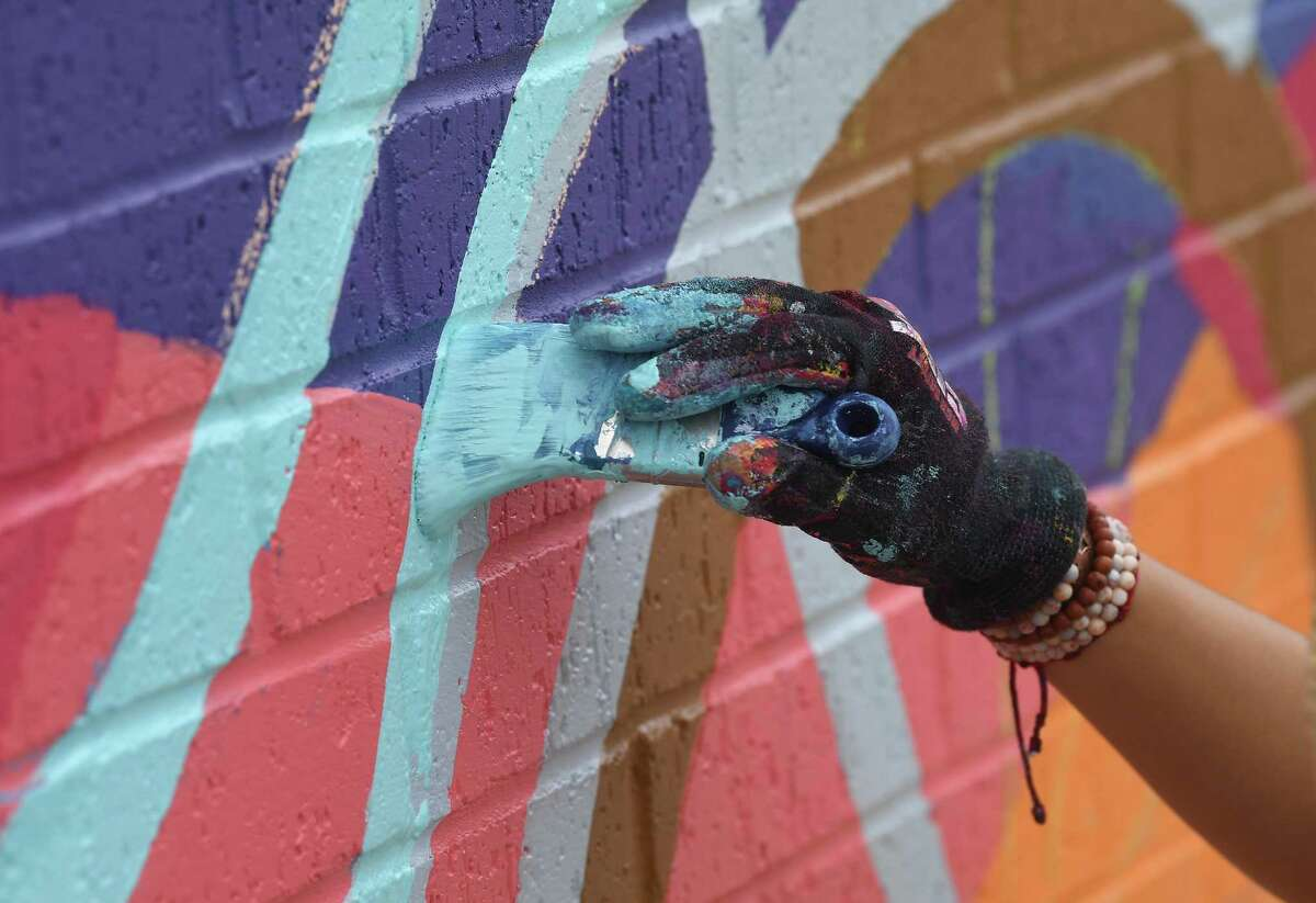 Ines Alvidres works on a large colorful mural outside the Beaumont Convention and Visitor's bureau office in downtown Beaumont Tuesday morning. The project is connected to the city's new rentable Beaucycles, which will be available following a kick-off event in July. Photo made Tuesday, June 1, 2021 Kim Brent/The Enterprise