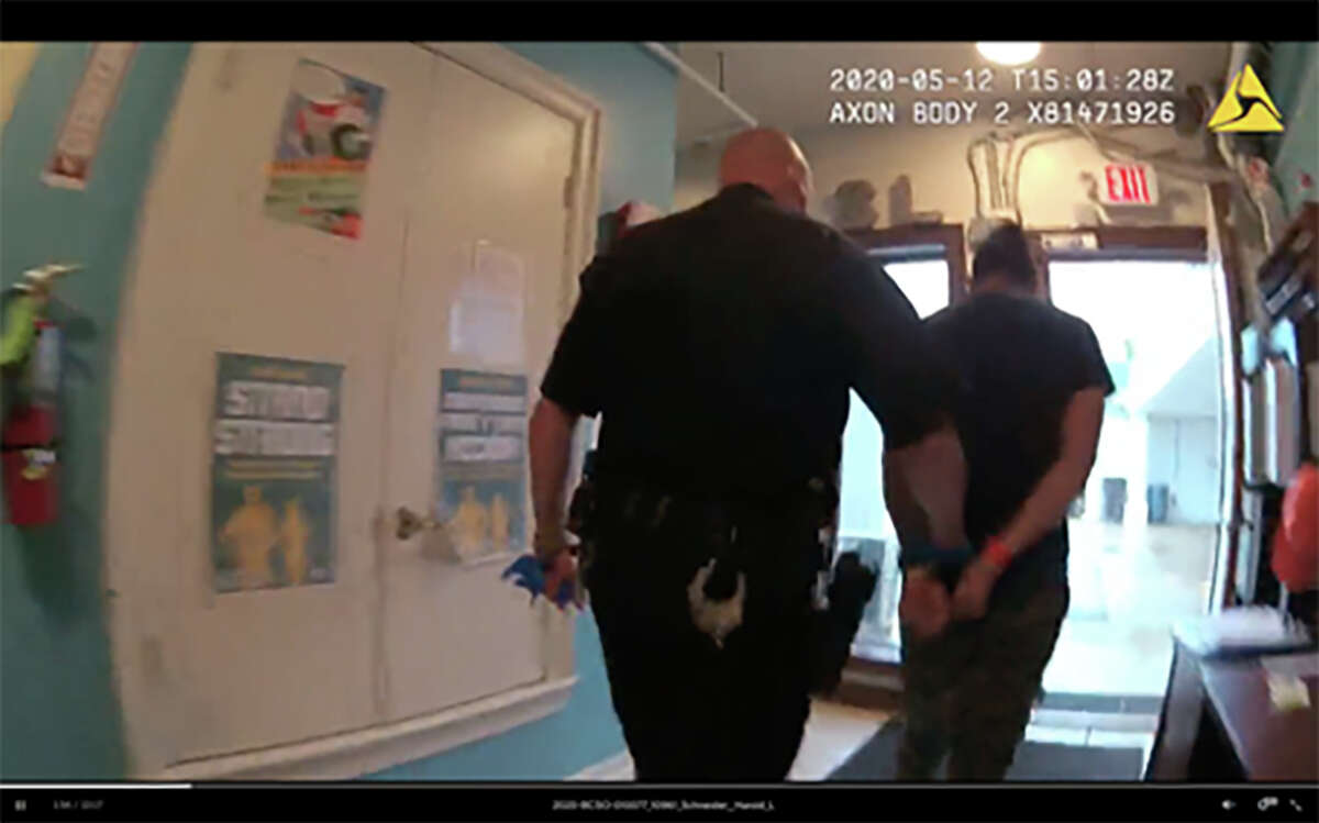 Bexar County Sheriff's Deputy Patrick Divers escorts a handcuffed 16-year-old boy out of a migrant children's shelter.