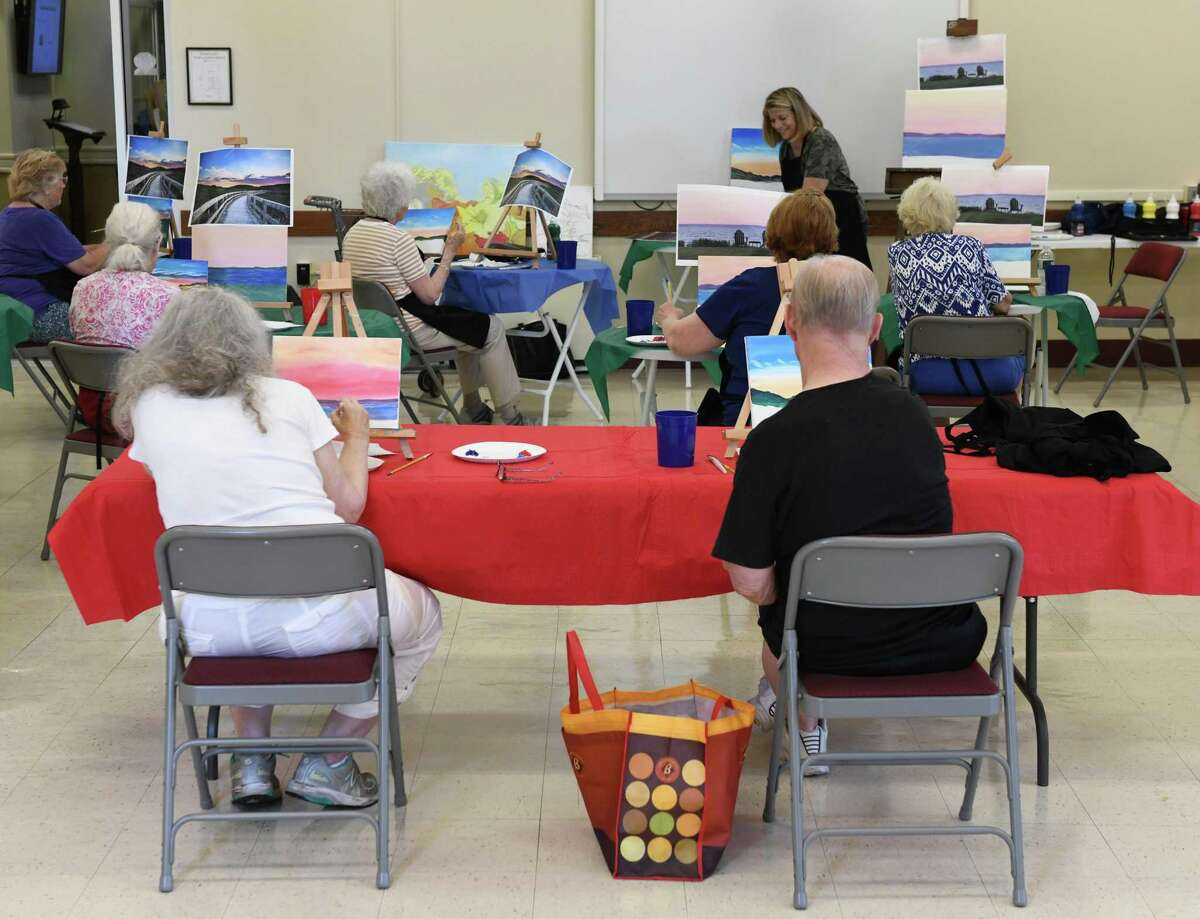 Participants paint during a class at the Greenwich Senior Center in Greenwich, Conn. Tuesday, June 8, 2021. The painting class, which started last week, is the first on-site, in-person activity available again at the Senior Center since it closed down for COVID more than a year ago.