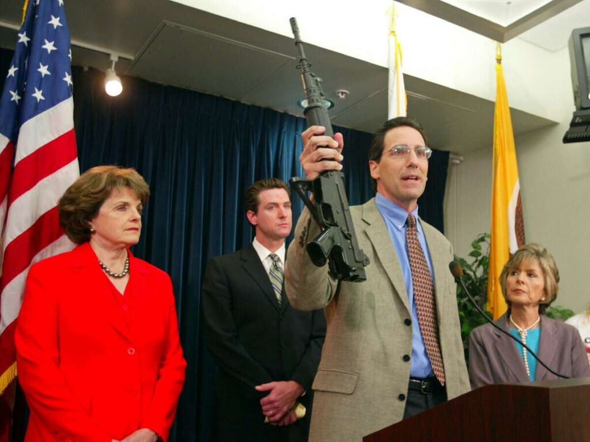 In this June 29, 2004, file photo, Steve Sposato, who lost his wife in a shooting, holds an automatic rifle as Sen. Dianne Feinstein, D-Calif., left, then San Francisco Mayor Gavin Newsom, second left, and Sen. Barbara Boxer, D-Calif., right, look on at a news conference in San Francisco. Sposato's wife, Jody Sposato, was killed in 1993 in the high-rise shooting at a San Francisco law firm.