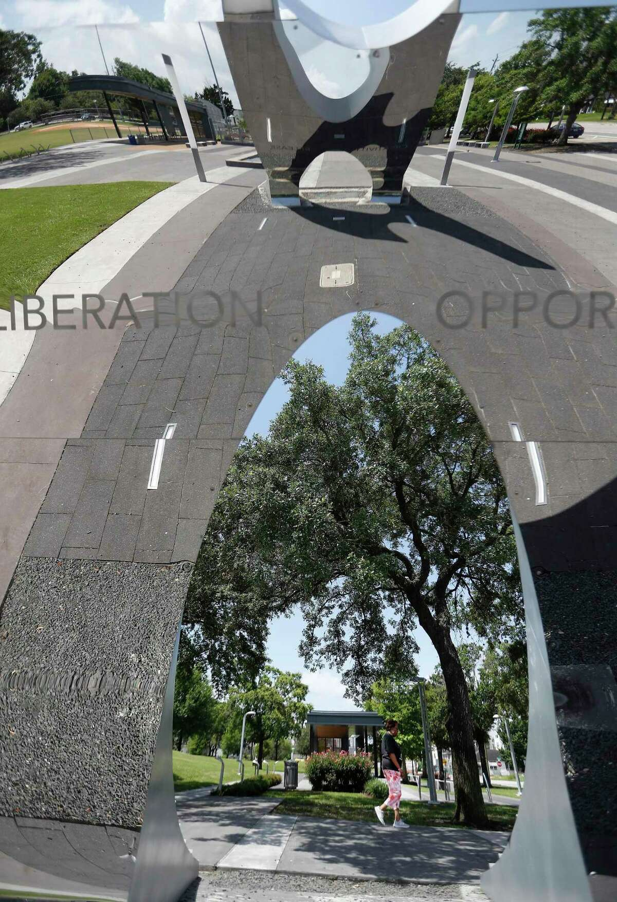 A woman walks past the reflection of a statue at Emancipation Park, Tuesday, June 8, 2021, in Houston, after volunteers cleaned the park.