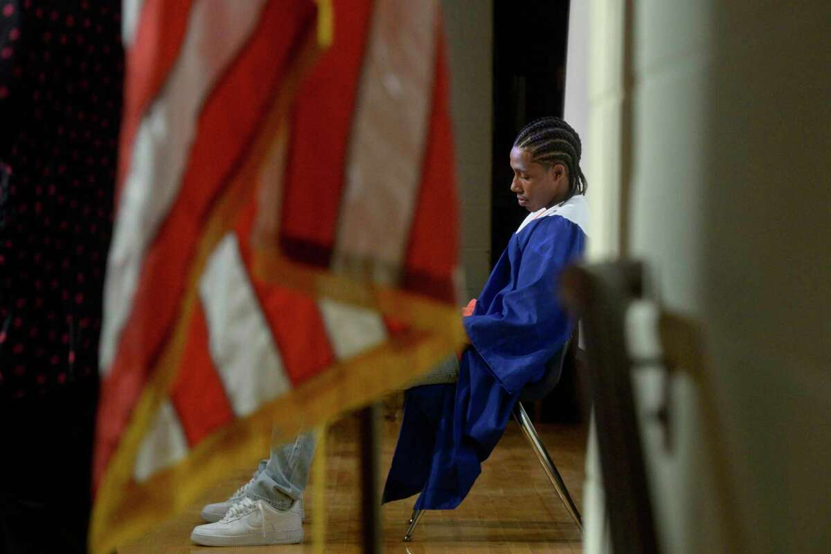 Graduate Raimir Rivera sits on stage and listens as his guidance teacher, Joanne Tolles, reads one of his poems during the Alternative Center for Excellence (ACE) 2021 graduation cermoney. Tuesday, June 8, 2021, at Broadview Middle School, Danbury, Conn.