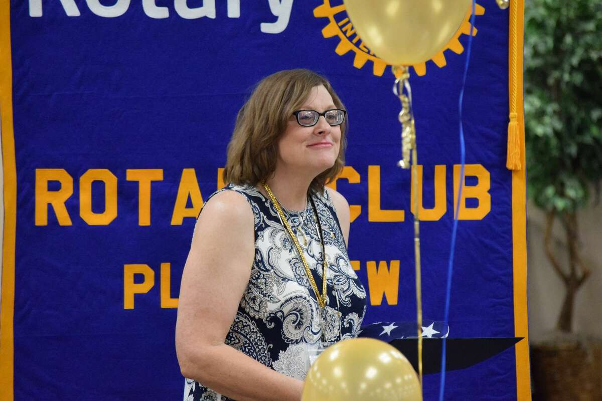 Plainview Rotary Club President Deana Sageser accepts a flag and recognition certificate from Congressman Jodey Arrington, a Plainview native (not pictured), during the Plainview Rotary Club's celebration of 100 years of existence.