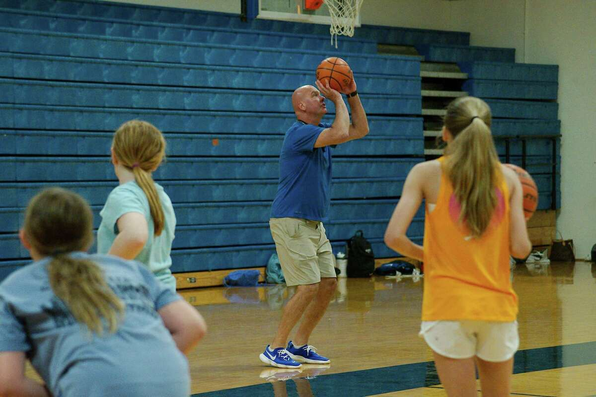 Peyton Franks, Alexis Spangle and Elaina Holtvluwer watch as Friendswood basketball coach Christian Thompson demonstrates a technique at the Friendswood summer basketball camp.