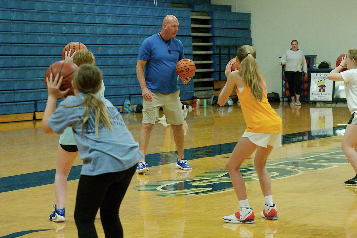 Peyton Franks, Alexis Spangle and Elaina Holtvluwer listen as Friendswood basketball coach Christian Thompson demonstrates a technique at the Friendswood summer basketball camp.