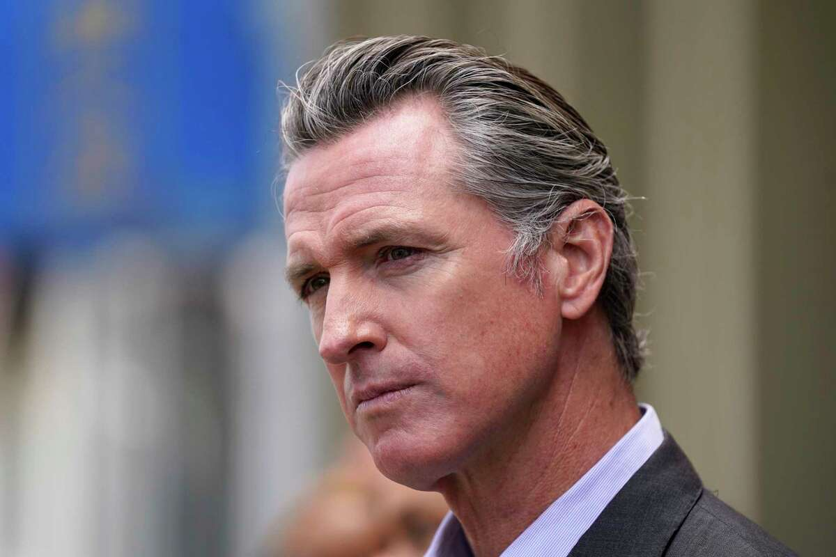 California Gov. Gavin Newsom listens to questions during a news conference outside a restaurant in San Francisco.