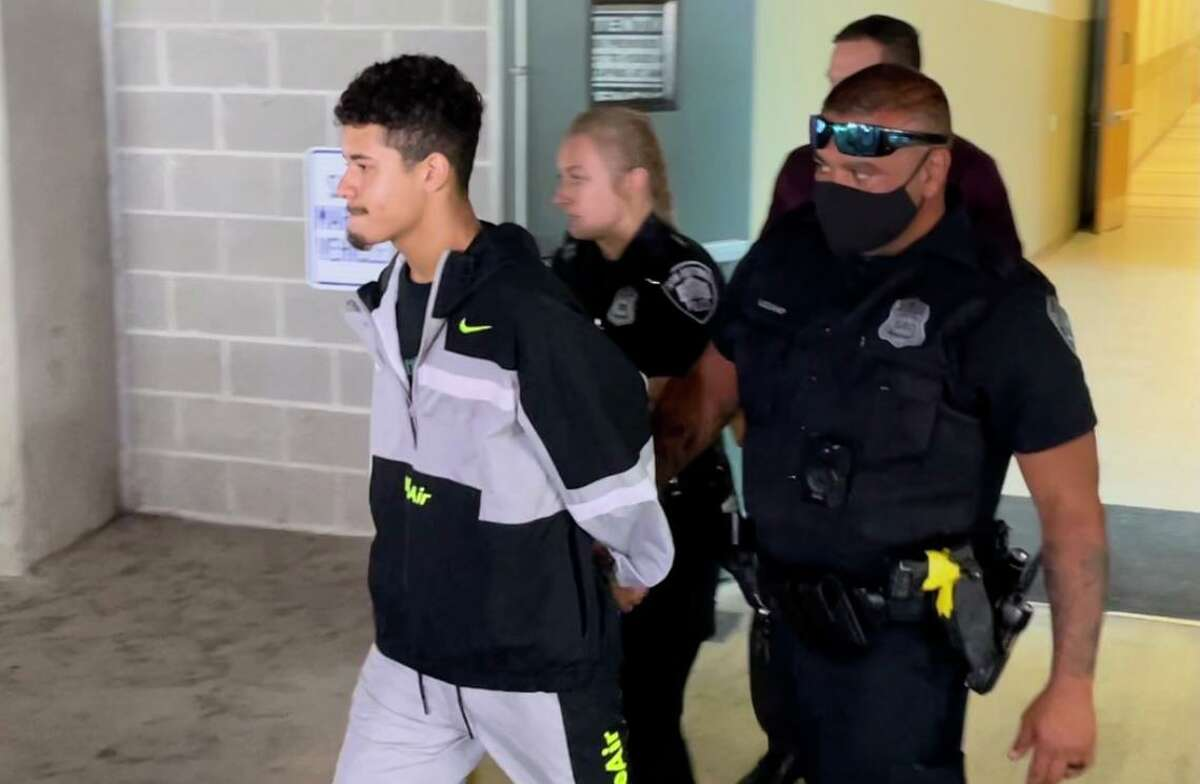 Avante Tyree Bird, 19, is led to a police vehicle at the Public Safety Headquarters. He was charged with aggravated assault with a deadly weapon in connection with a Saturday shooting in the Alamo Plaza area that injured at least two people, according to San Antonio police.