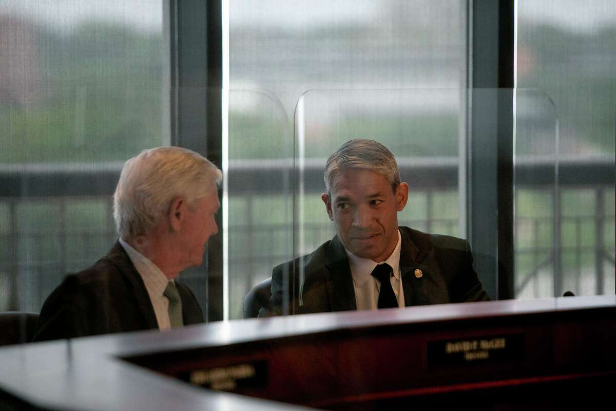 San Antonio Mayor Ron Nirenberg, right, talks with San Antonio Water System Board of Trustees vice chairman David McGee as the Board recesses for an executive session during their meeting at the SAWS administrative offices on June 8, 2021.