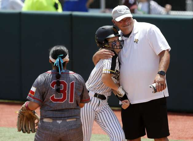 Hollie Thomas #6 of Liberty gets a hug from assistant coach Joe Slack after hitting an RBI single in the third inning of the Class 4A UIL state championship game at Red & Charline McCombs Field, Saturday, June 5, 2021, in Austin. Photo: Jason Fochtman/Staff Photographer / 2021 ? Houston Chronicle