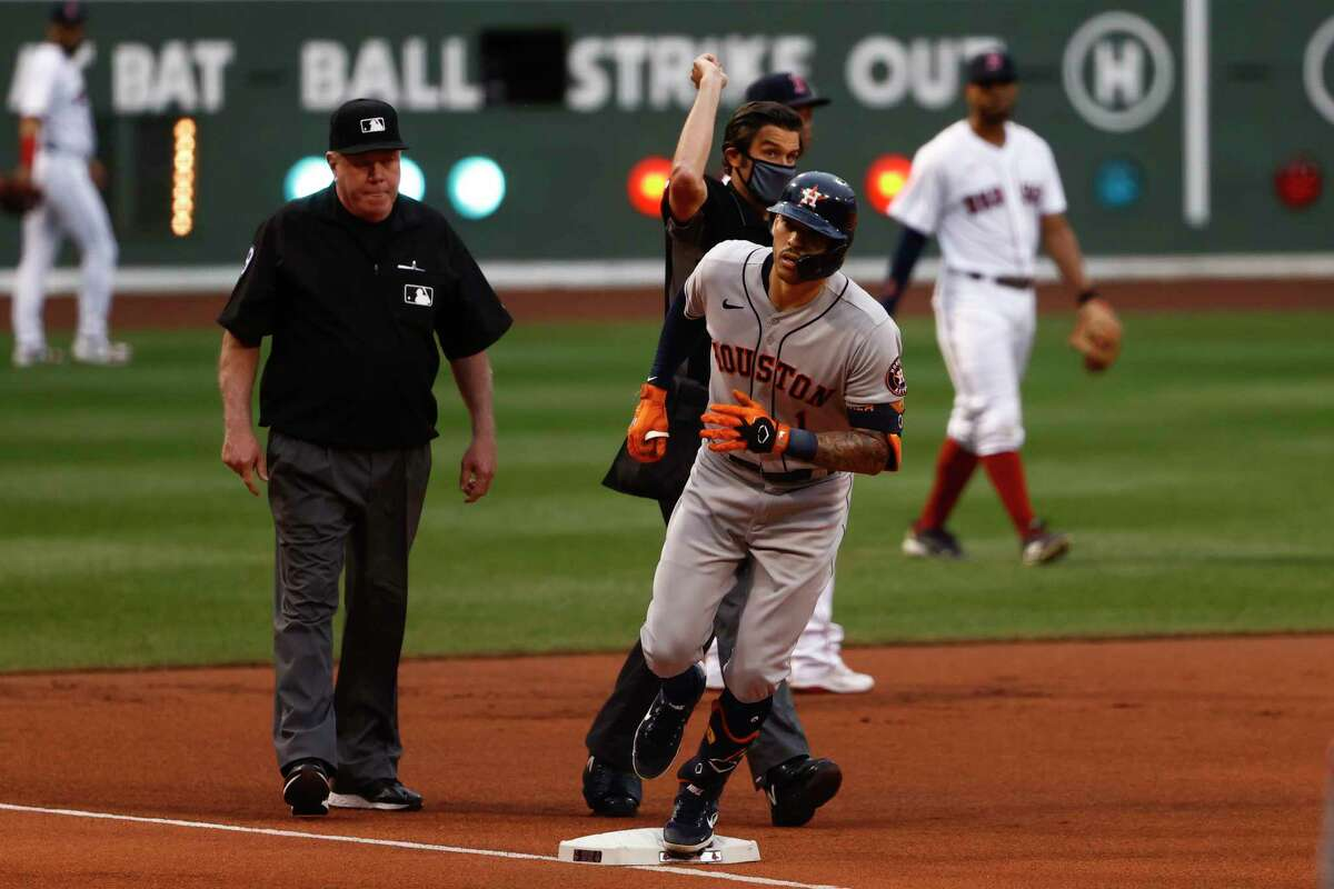 Houston Astros' Carlos Correa rounds the bases as umpire John Tumpane signals home run after conferring with umpire Brian Gorman, left, during the first inning of a baseball game against the Boston Red Sox Tuesday, June 8, 2021, at Fenway Park in Boston. (AP Photo/Winslow Townson)