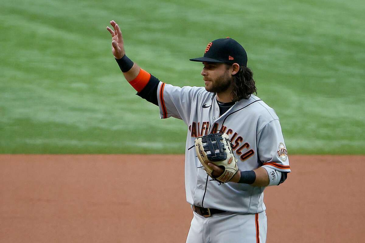 ARLINGTON, TEXAS - JUNE 08: Brandon Crawford #35 of the San Francisco Giants acknowledges his teammates and fans while being recognized for setting a franchise record playing 1,326 games as shortstop with the Giants in the bottom of the first inning at Globe Life Field on June 08, 2021 in Arlington, Texas. (Photo by Tom Pennington/Getty Images)
