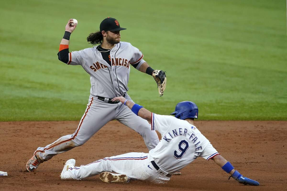San Francisco Giants shortstop Brandon Crawford throws to first to complete the double play after forcing Texas Rangers' Isiah Kiner-Falefa (9) at second in the third inning of a baseball game in Arlington, Texas, Tuesday, June 8, 2021. Willie Calhoun was out at first. (AP Photo/Tony Gutierrez)