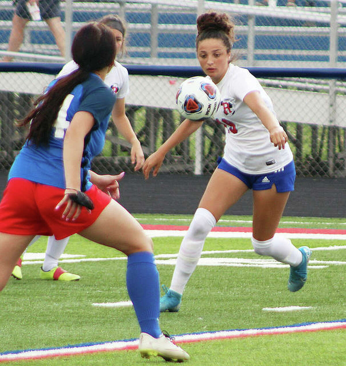 Roxana's Kendall Kamp, right, eyes the ball as she readies to take a shot in Tuesday's night's 4-0 win over Carlinville in a Class 1A sectional semifinal at CHS. Kamp scored three of the Shells' four goals.