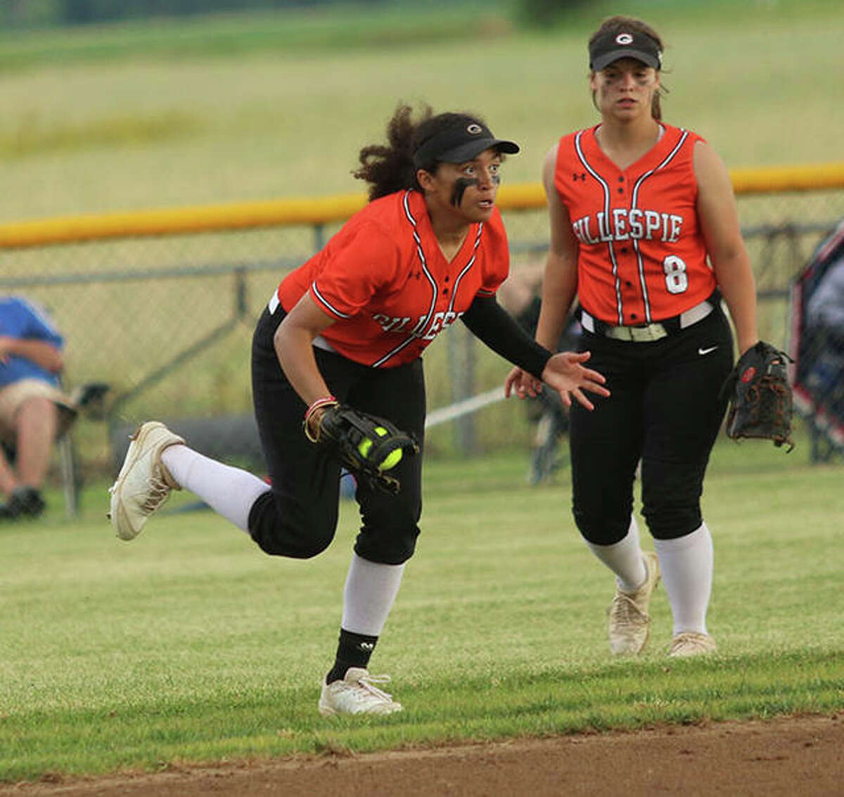 Gillespie left fielder Shelby Taylor (left) makes a running catch of a flyball blown back in just off the infield while Chloe Segarra watches the play Tuesday in a Class 2A sectional semifinal in Gillespie.