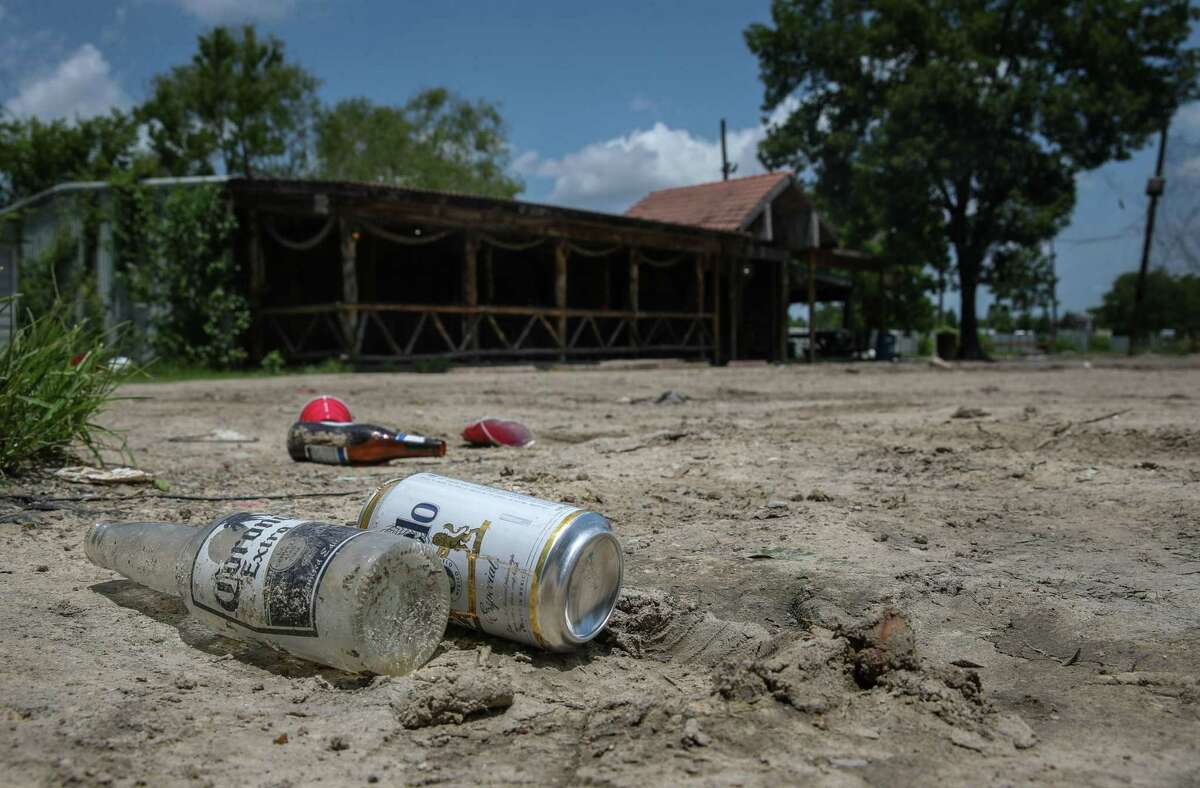 Trash sits Tuesday in a lot where a bar once operated on Hill Road in Houston. Court documents detail how the March 2020 abduction of a woman from the bar led police to raid a nearby home and discover a human-smuggling operation.