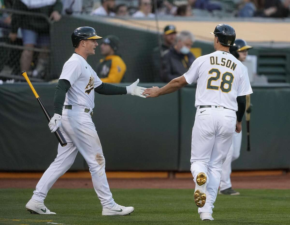 Oakland Athletics' Matt Olson (28) is congratulated by Matt Chapman, left, after scoring on a single by Chad Pinder during the fourth inning against the Arizona Diamondbacks in a baseball game Tuesday, June 8, 2021, in Oakland, Calif. (AP Photo/Tony Avelar)