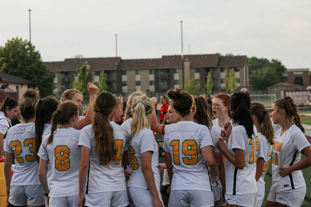 Dow High's girls' soccer team breaks down the huddle before its regional semifinal against Hudsonville at Grandville High School on Tuesday, June 8, 2021.