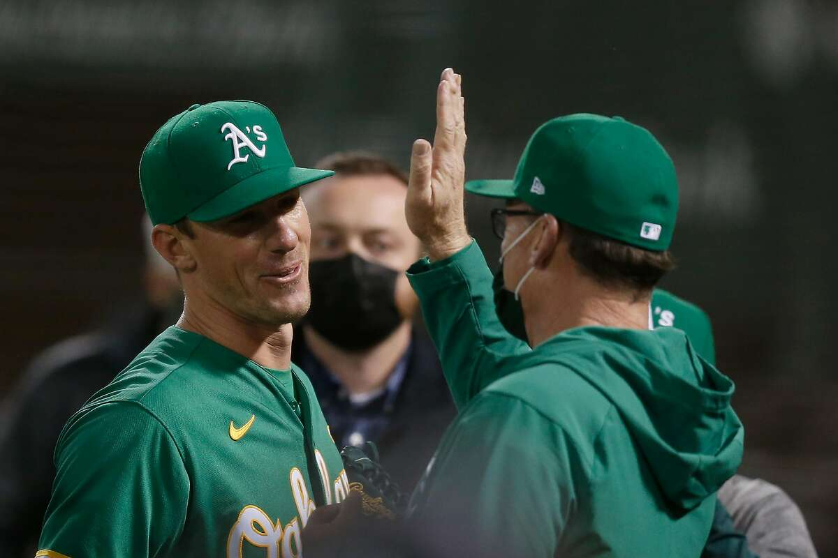 OAKLAND, CALIFORNIA - MAY 27: Starting pitcher Chris Bassitt #40 of the Oakland Athletics celebrates with manager Bob Melvin #6 after throwing a complete game against the Los Angeles Angels at RingCentral Coliseum on May 27, 2021 in Oakland, California. The Athletics defeated the Angels 5-0. (Photo by Lachlan Cunningham/Getty Images)