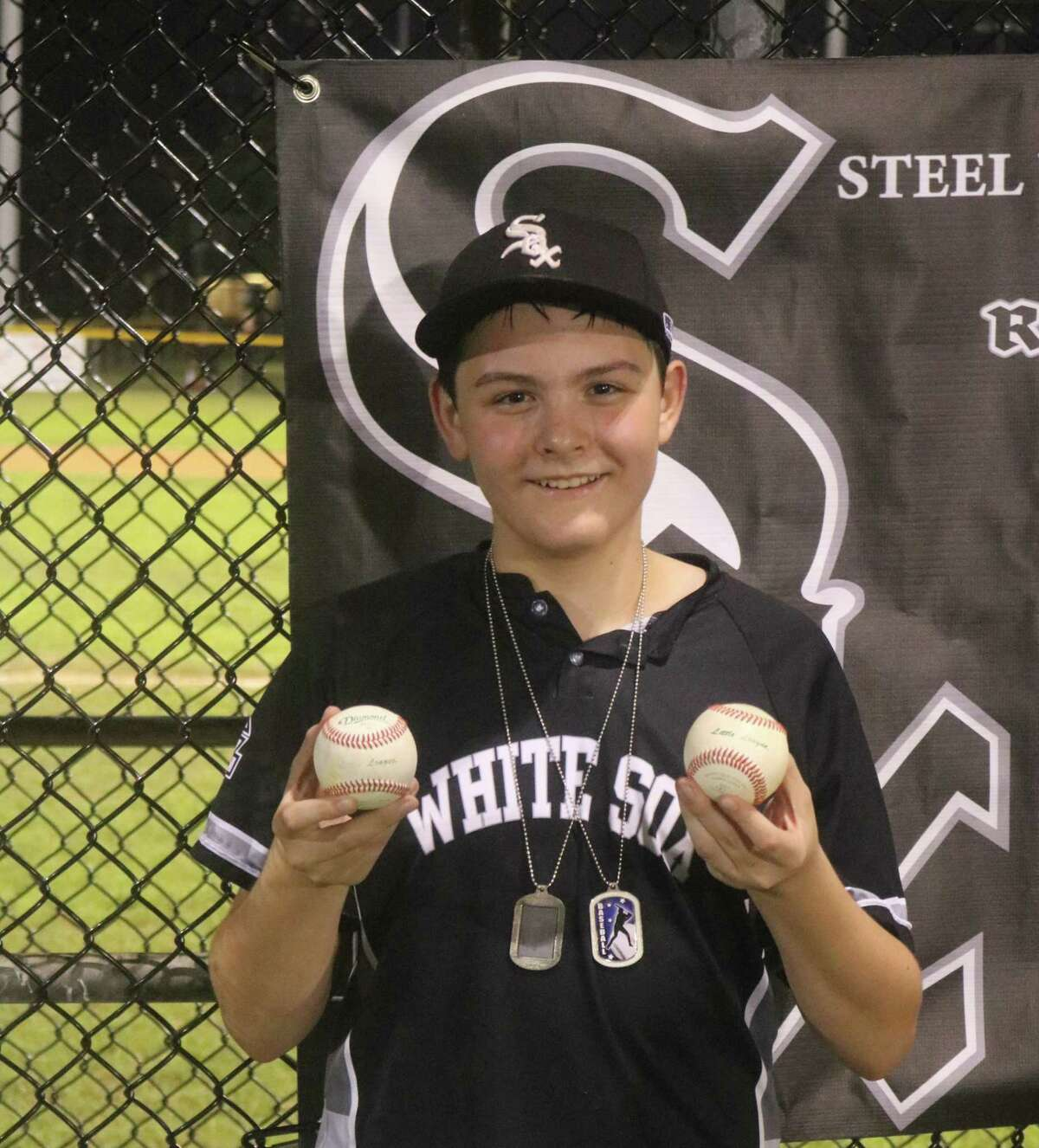 Jason Upshaw holds the two baseballs he sent flying out of Joseph Fleming Field Tuesday night. It deposited the team in the Final Four for the Majors Division.