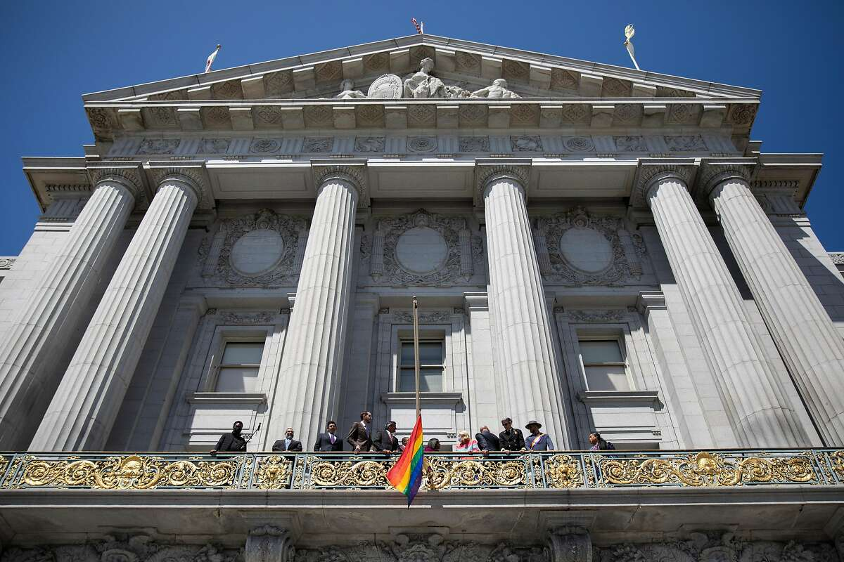 San Francisco city and state officials gather on the Mayor's balcony to ceremonially raise the rainbow Pride flag during a Pride month kickoff celebration outside of San Francisco City Hall in San Francisco, Calif. Monday, June 7, 2021.