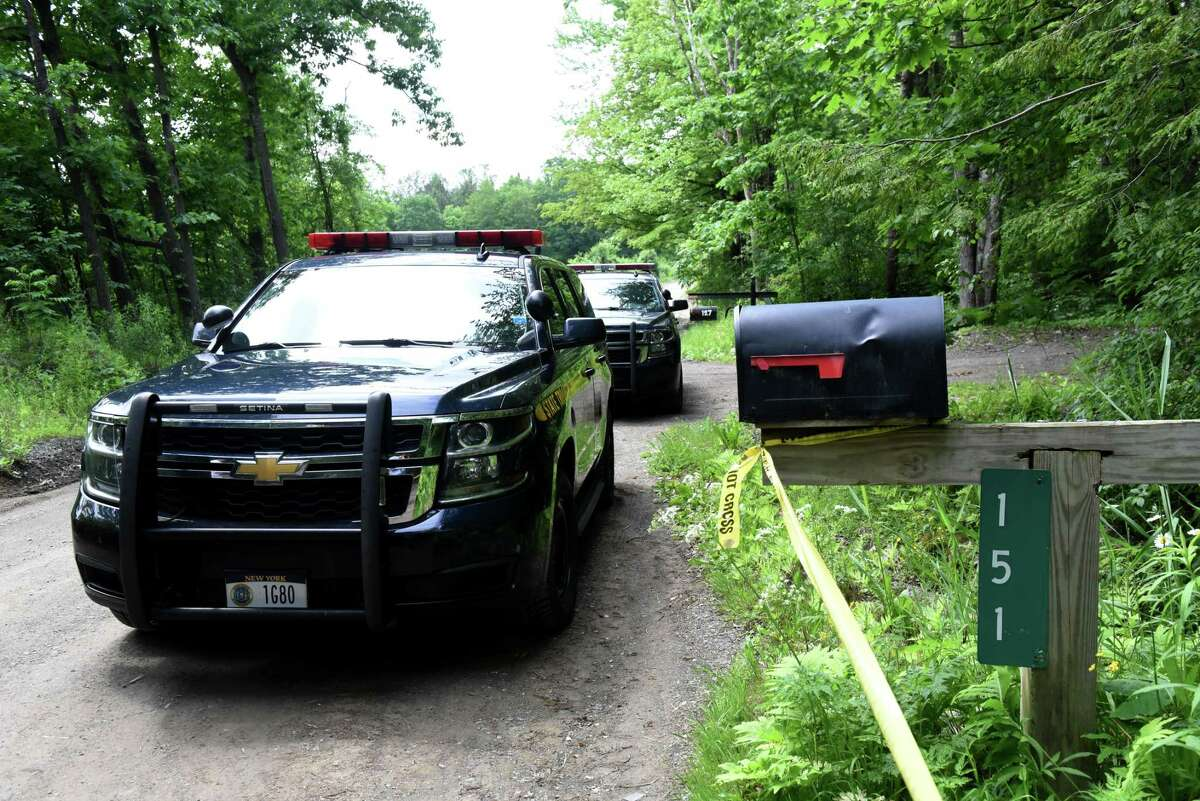 New York State State Police cars are parked along Jay Herrington Road where they are investigate the scene of a homicide on Wednesday, June 9, 2021, in Pittstown, N.Y. (Will Waldron/Times Union)