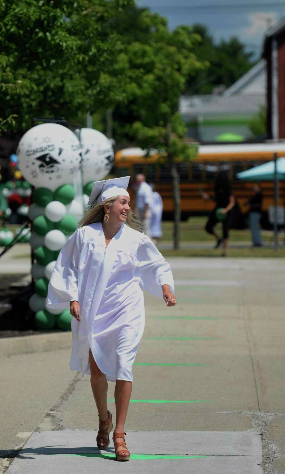 Graduate Amanda Leigh Clark looks over to her family's car as she walks to receive her diploma at the 2020 New Milford High School graduation ceremony on Saturday. The graduates paraded from Sarah Noble Intermediate School to the high school and walked the sidewalk to receive their diplomas. June 20, 2020, in New Milford, Conn.