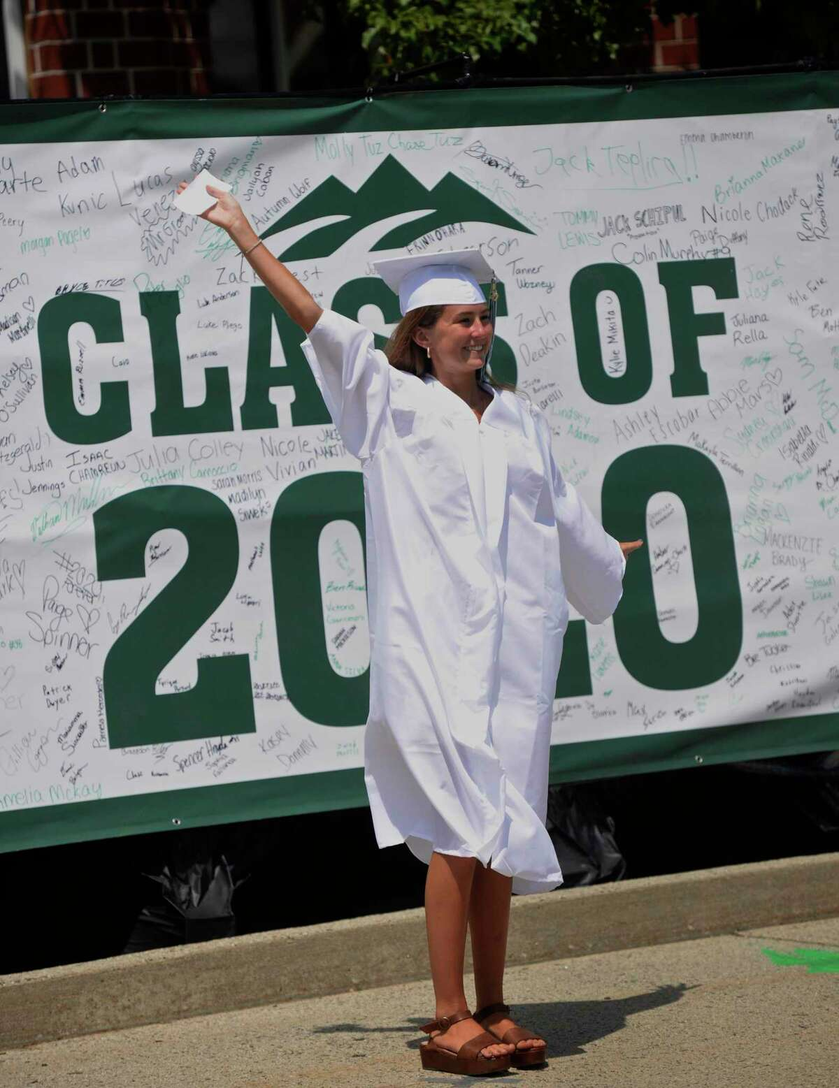 Graduate Erinn Elizabeth O'Hara poses for a photograph at the 2020 New Milford High School graduation ceremony on Saturday. The graduates paraded from Sarah Noble Intermediate School to the high school and walked the sidewalk to receive their diplomas. June 20, 2020, in New Milford, Conn.