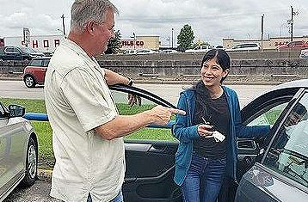 Greg Zak attends to a customer seeking a vehicle at his car dealership Dixon Motor Cars on the North Freeway. Zak said his inventory is down by 50 percent because of the pandemic.