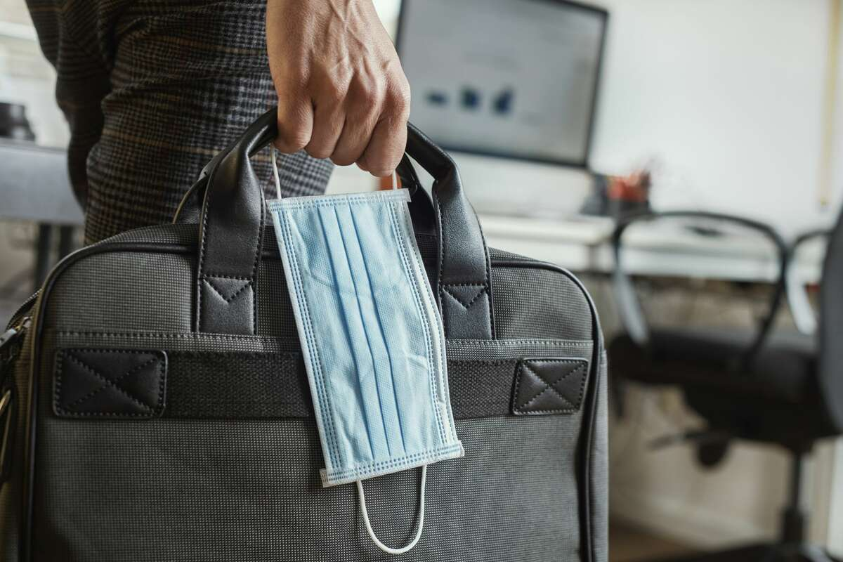 Closeup of a young man in an office holding a briefcase and a surgical mask in his hand.