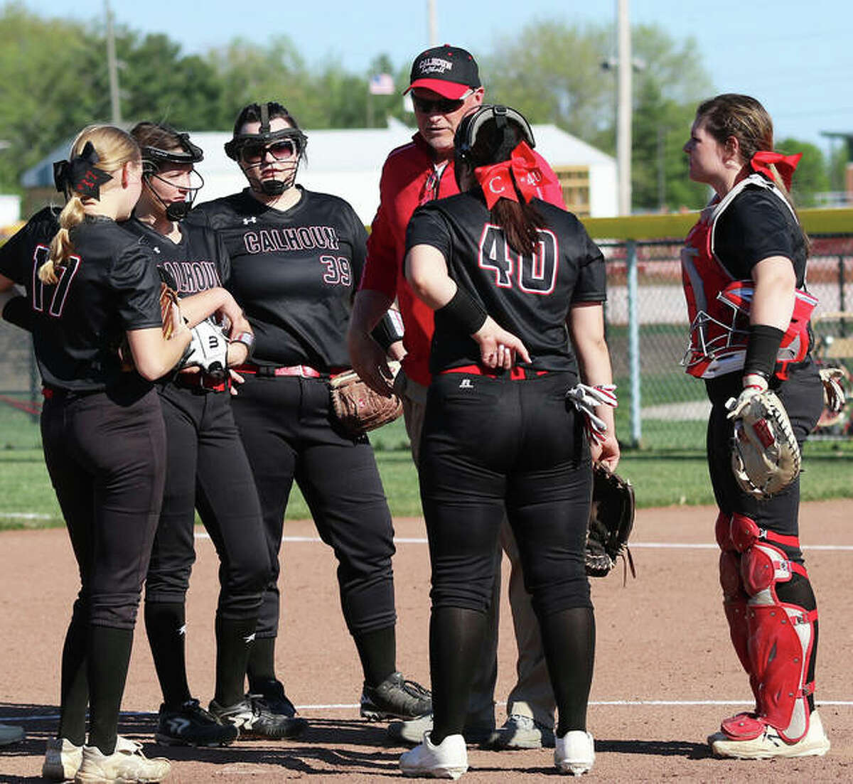 Calhoun coach Duane Sievers meets with some Warriors in a meeting at the pitcher's circle in a game earlier this season. The Warriors finished the season 14-9 with Tuesday's sectional defeat in Centralia.