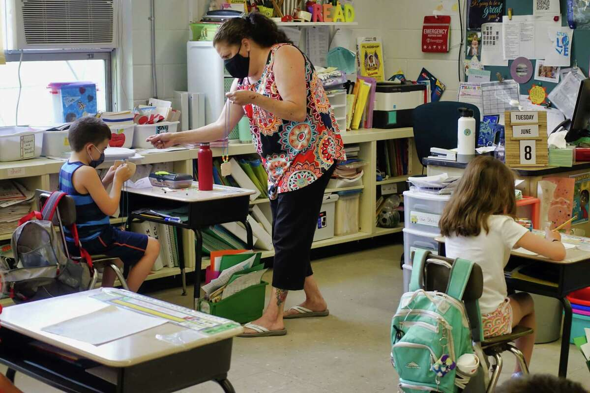 First Grade classroom aide Haley Buttars helps to guide a student making a necklace without touching the students material he is using at Karigon Elementary School on Tuesday, June 8, 2021, in Clifton Park, N.Y. (Paul Buckowski/Times Union)