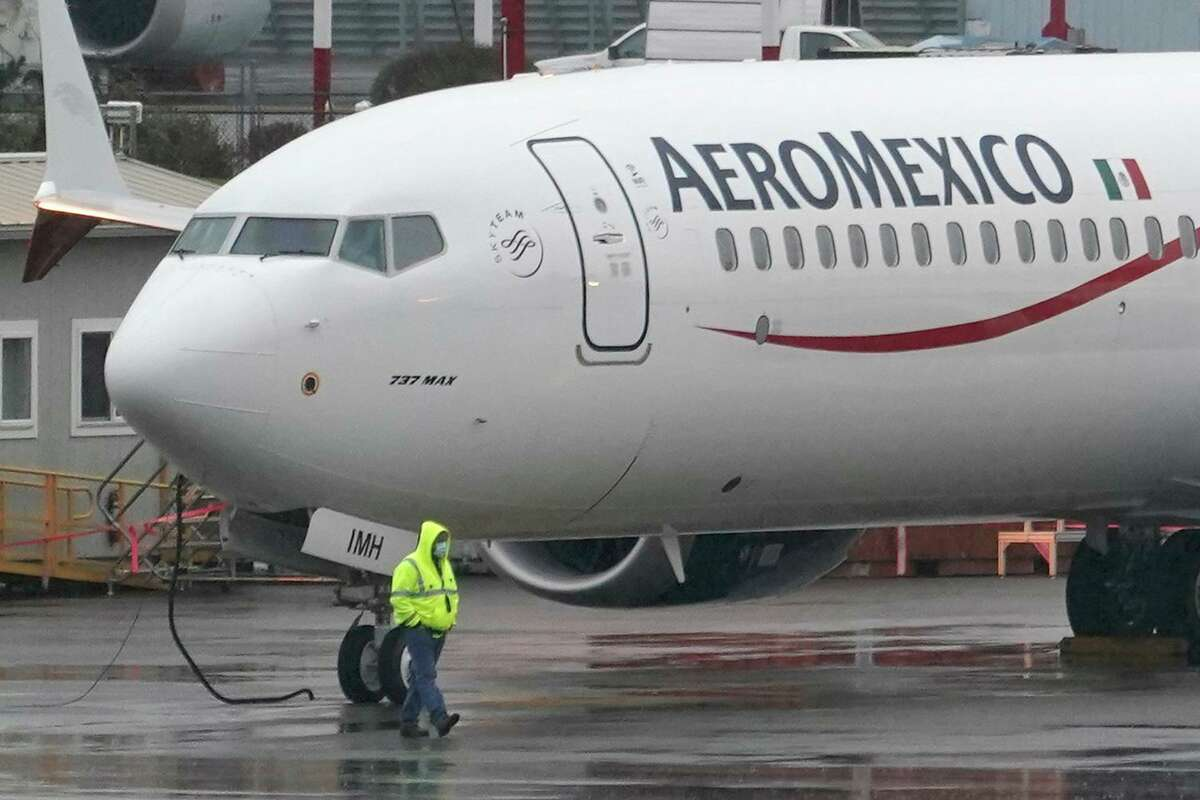 FILE - In this Nov. 18, 2020 file photo, a worker wearing a mask walks past a Boeing 737 Max 9 built for Aeromexico as it is prepared for a flight from Renton Municipal Airport, in Renton, Wash. U.S. regulators have downgraded Mexico's aviation safety rating, Tuesday, May 25, 2021, a move that prevents Mexican airlines from expanding flights to the United States just as travel is recovering from the pandemic. (AP Photo/Ted S. Warren, File)