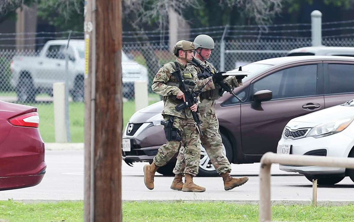 Lackland security personnel are seen carrying weapons as they walk through a parking lot as JBSA-Lackland was on lockdown on Wednesday, June 9, 2021 on reports of an active shooting situation. Military Police, San Antonio Police Department and Texas State Troopers could be seen at the Valley Hi entrance of the base.