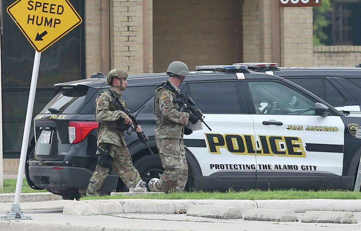 Lackland security personnel are seen carrying weapons as they walk past a SAPD police vehicle as JBSA-Lackland was on lockdown on Wednesday, June 9, 2021 on reports of an active shooting situation. Military Police, San Antonio Police Department and Texas State Troopers could be seen at the Valley Hi entrance of the base.
