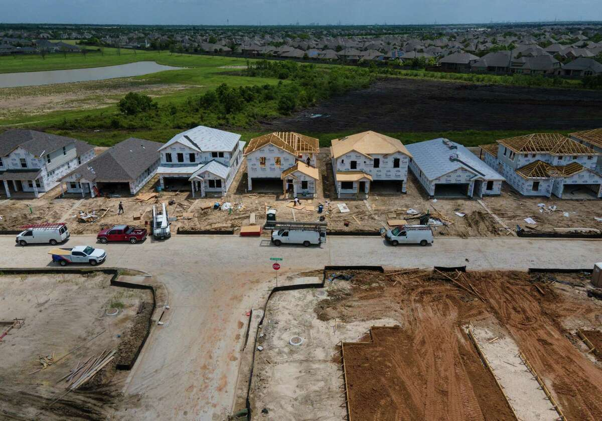 People build homes in the Grand Trails subdivision Wednesday, June 9, 2021, in Richmond. Builders plan to construct 129 homes in the subdivision.