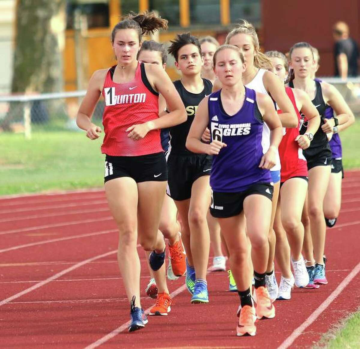 Staunton's Lydia Roller (left) and CM's Hannah Meiser (right) run on the lead in the opening lap of the 3,200 meters on Friday at the EA-WR Class 2A Sectional in Wood River.