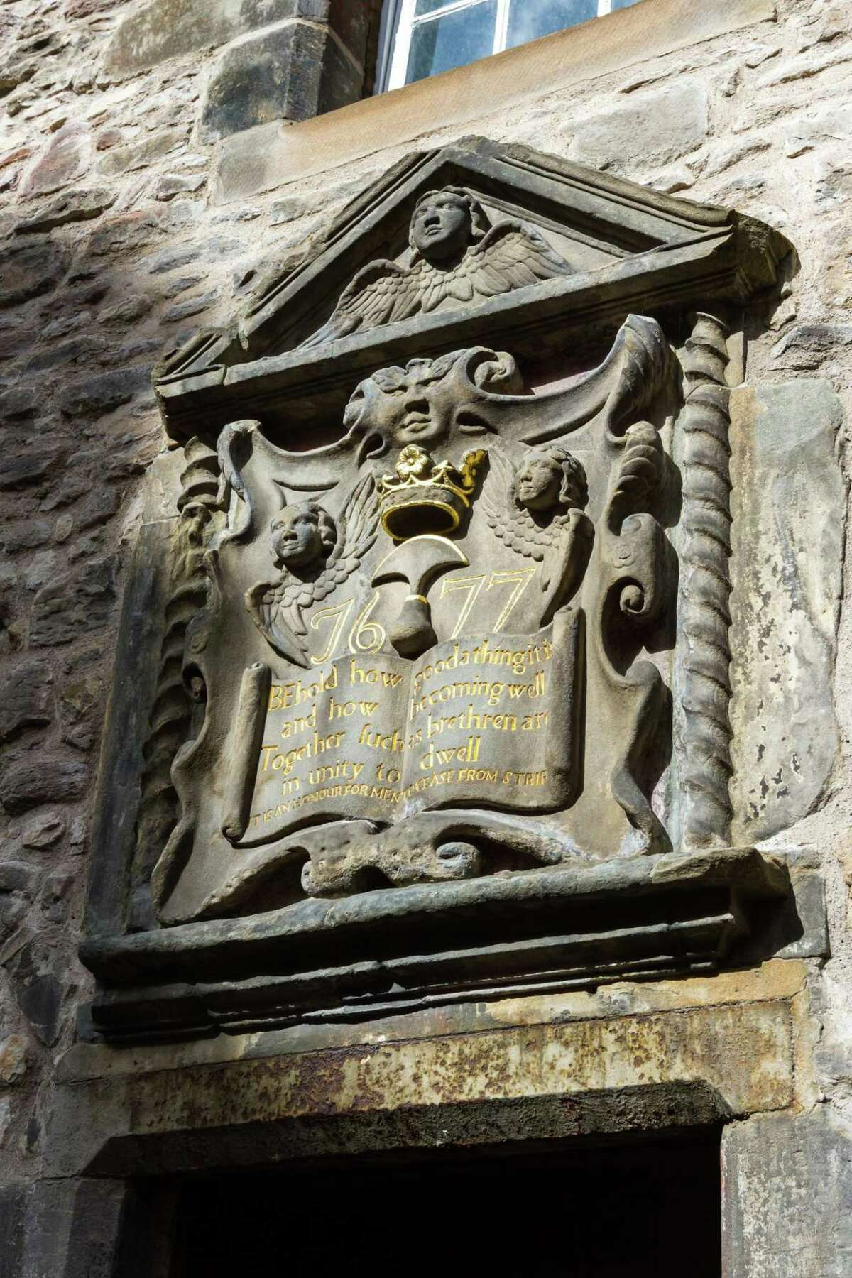Psalm 133 chiseled into a stone book above the Canongate doors Edinburgh.