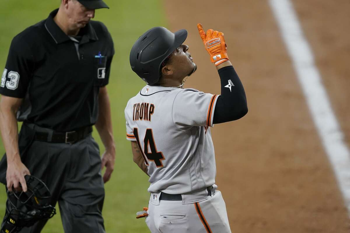 San Francisco Giants' Chadwick Tromp celebrates his solo home run as he crosses the plate as umpire Shane Livensparger, left, looks on in the fifth inning of the team's baseball game against the Texas Rangers in Arlington, Texas, Wednesday, June 9, 2021. (AP Photo/Tony Gutierrez)