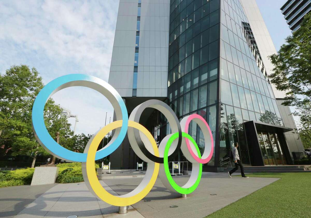 A man walks past the Olympic rings in Tokyo, on Monday, June 7, 2021.
