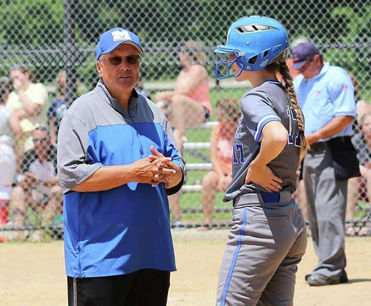 Marquette coach Dan Wiedman (left) talks with Abby Porter before she bats in a Class 2A regional title game Saturday in Alton.