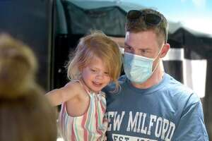 Dakota Rabito, age 3, picks out her ice cream, strawberry with rainbow sprinkles, with her father Jeff Rabito, an Emergency Room (ER) Technician at New Milford Hospital. The hospital had an ice cream social as part of its celebration of 100 years of service. Wednesday, June 9, 2021, in New Milford, Conn.