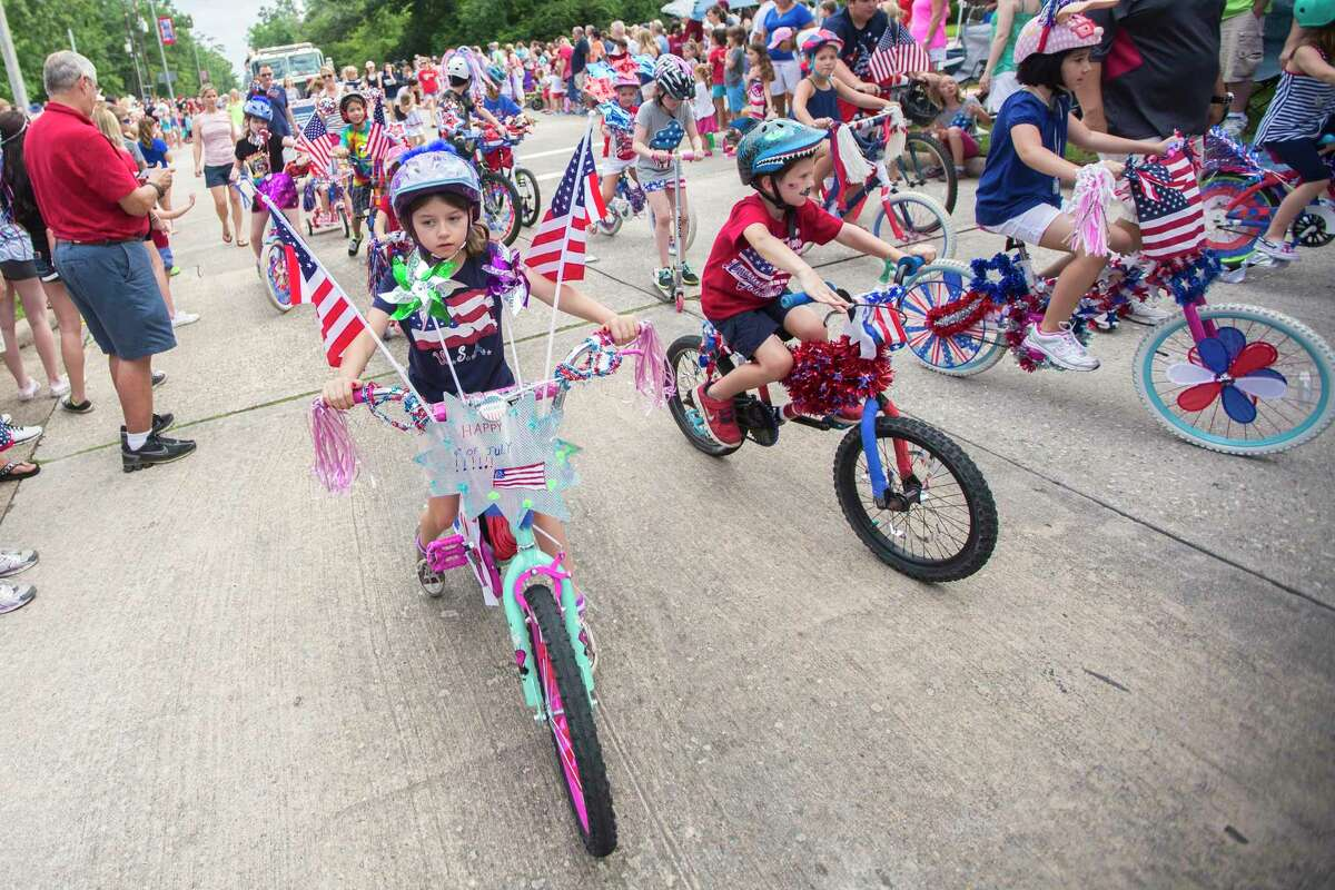 A pack of cyclists down West Lake Houston Parkway during a previous Kingwood Civic Club Fourth of July parade in Kingwood.